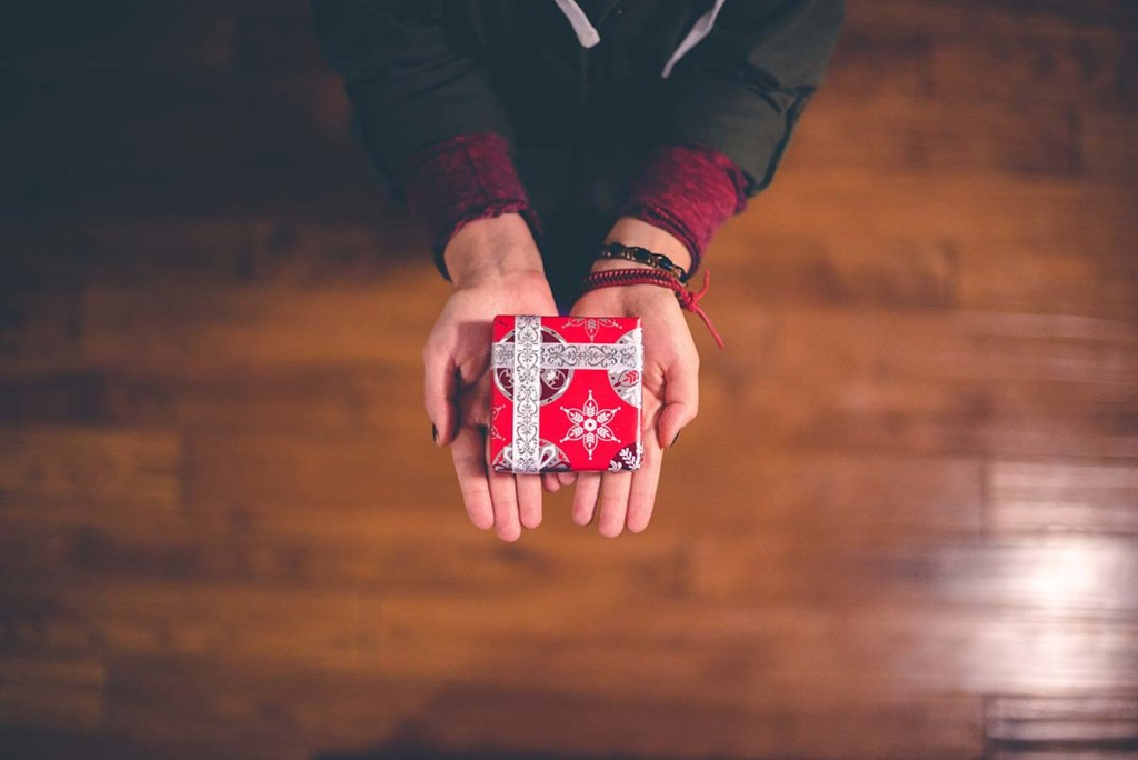 A person holding a small box wrapped in red holiday wrapping paper.
