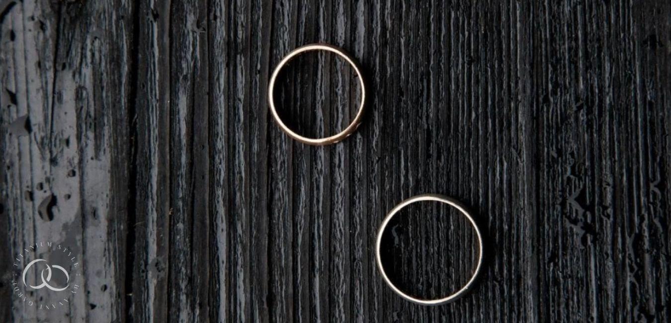 Two titanium wedding rings sitting on a dark wood background